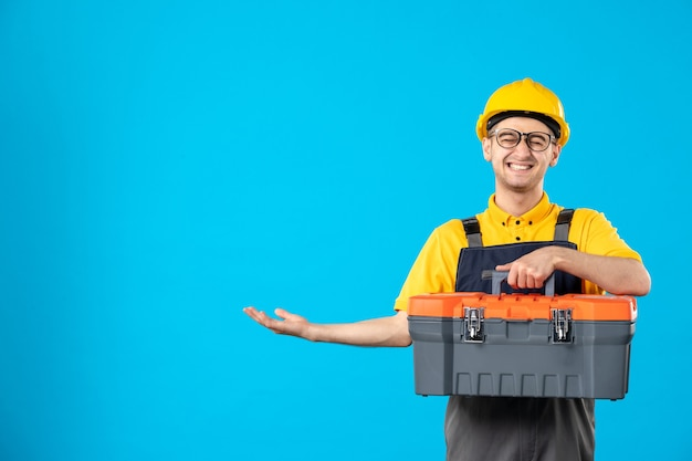 Front view laughing male builder in uniform and helmet with tool box on blue