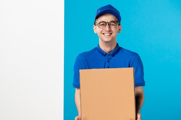 Front view of laughing male courier in blue uniform with pizza on blue wall