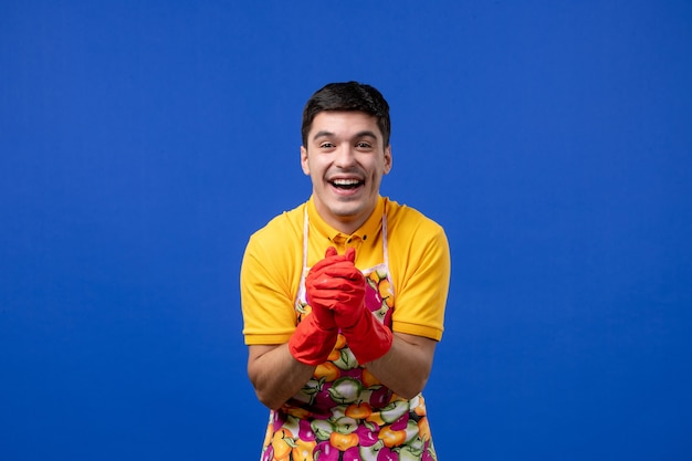 Front view laughing male housekeeper in apron joining hands together