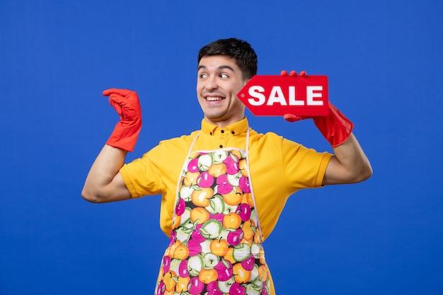Vista frontale che ride governante maschio con guanti di scarico rossi con cartello di vendita su spazio blu