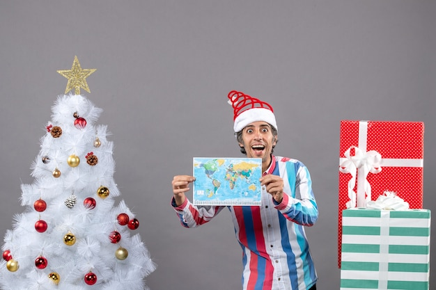 白いクリスマスツリーの近くに地図を保持し、コピースペースを提示して目を大きく開いて笑っている男の正面図