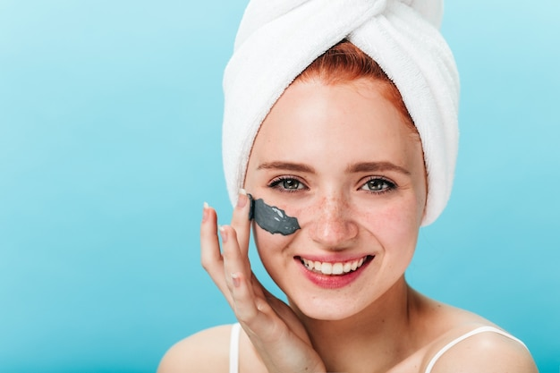Front view of laughing woman applying face mask. studio shot of european girl doing skincare with smile.