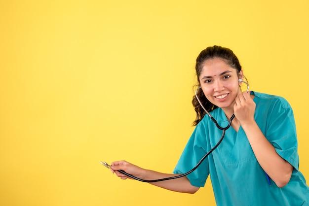 黄色の背景に聴診器を保持している制服を着た女性医師を笑っている正面図