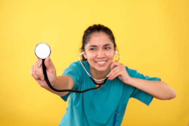 Medico della donna di risata di vista frontale in stetoscopio uniforme della holding su priorità bassa gialla