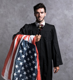 Front view lawyer in robe with american flag and gavel