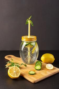Una vista frontale cocktail al limone bevanda fresca fresca all'interno della tazza di vetro a fette e limoni interi cetrioli con fiori paglia sullo sfondo scuro cocktail drink frutta