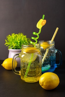 Una bevanda fresca fresca del cocktail di limone di vista frontale dentro le tazze di vetro affettate e le intere cannucce sui precedenti scuri bevono la frutta del cocktail