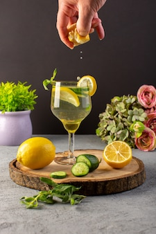 Una vista frontale cocktail al limone bevanda fresca fresca all'interno del bicchiere ottenendo un po 'di succo di limone fette limoni paglia sulla scrivania in legno e sfondo grigio cocktail drink frutta