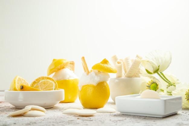 白いテーブルジュースの柑橘類のカクテルにクッキーと正面図レモンカクテル