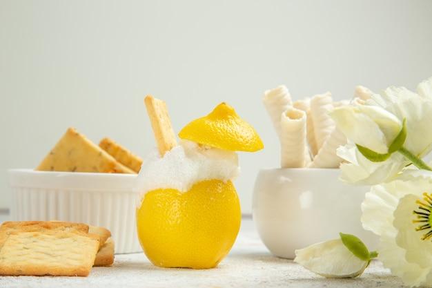 白いテーブルの上のクラッカーとレモンカクテルの正面図柑橘類のカクテルジュース