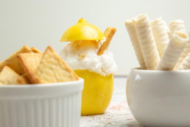 Cocktail al limone vista frontale con ghiaccio e cracker su succo di cocktail di agrumi da tavola bianca