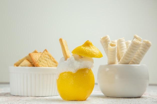 Cocktail al limone vista frontale con ghiaccio su succo di cocktail di agrumi da tavola bianca