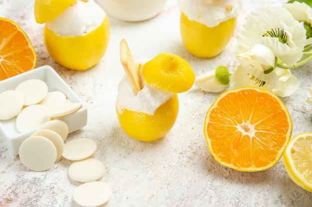 Лимонные коктейли с фруктами на белом столе, цитрусовый коктейль, вид спереди