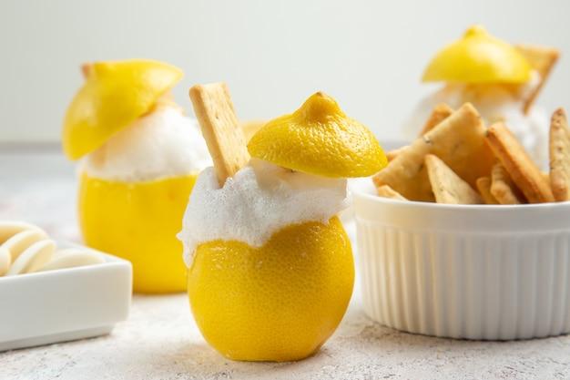 Лимонные коктейли со льдом и крекерами на белом столе, цитрусовый коктейльный сок, вид спереди