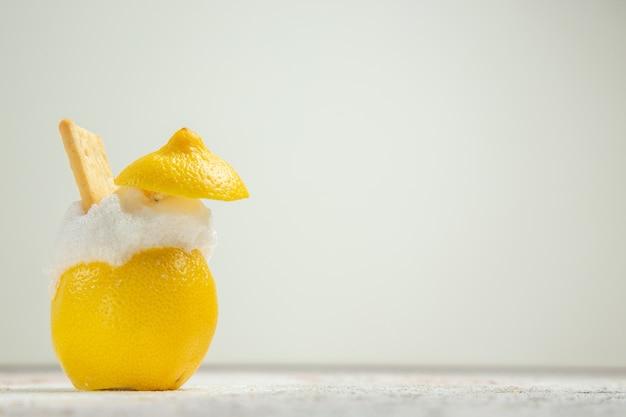 Лимонные коктейли со льдом на белом столе, вид спереди, сок цитрусовых коктейлей