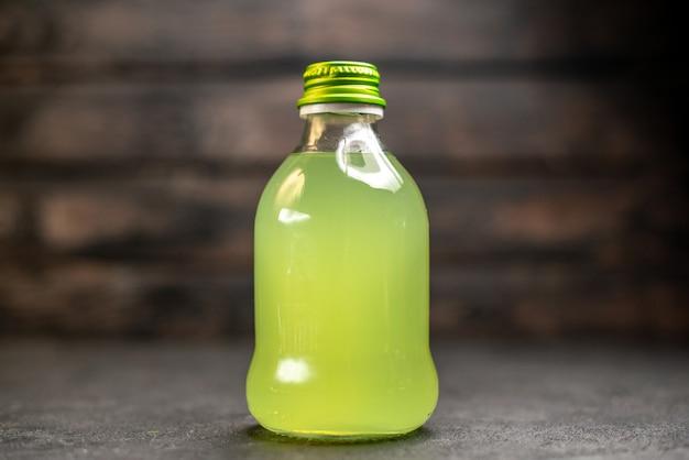 Bottiglia di limonata vista frontale su superficie in legno
