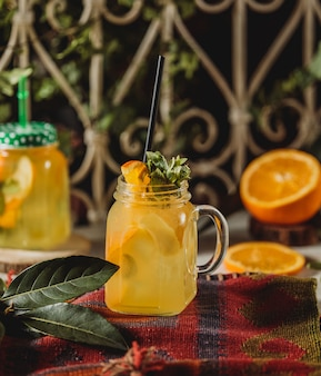 Front view of lemonade drink with sliced orange and lemon decorated with mint in cocktail glass with handle and straw on a tablecloth