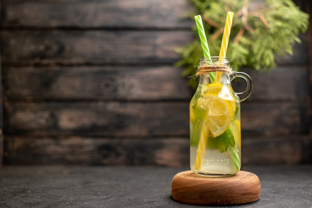 Limonata vista frontale aromatizzata da pipette gialle e verdi di menta su piante in vaso di legno sulla superficie