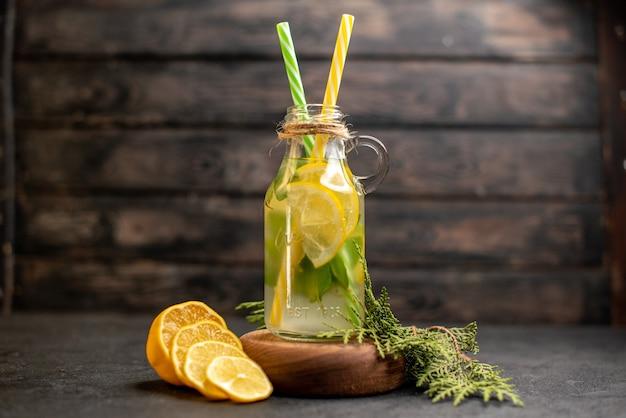 Желтые и зеленые пипетки лимонада на деревянной доске, вид спереди, нарезанные лимоны на деревянной поверхности