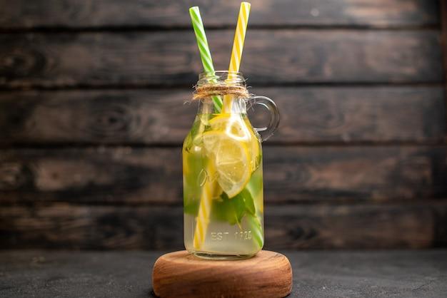 Vista frontale pipette gialle e verdi di limonata su tavola di legno su superficie di legno