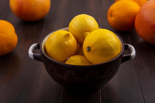 Limoni vista frontale in una ciotola con arance e pompelmi su uno sfondo di legno