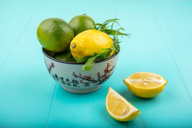 Front view of lemons on a bowl with tarragon on blue surface