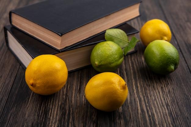 ライムと木製の背景の本とレモンの正面図