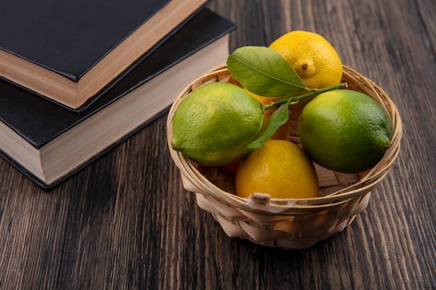 Limoni di vista frontale con la merce nel cestino e libri di lime su fondo di legno