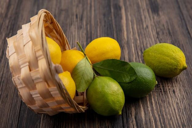 Limoni vista frontale con limette in un cesto capovolto su uno sfondo di legno