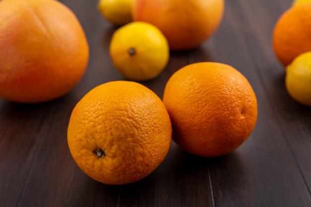 木の背景にオレンジとグレープフルーツと正面図レモン
