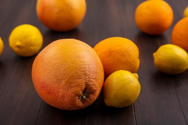 Лимоны с апельсинами и грейпфрутами на фоне дерева, вид спереди