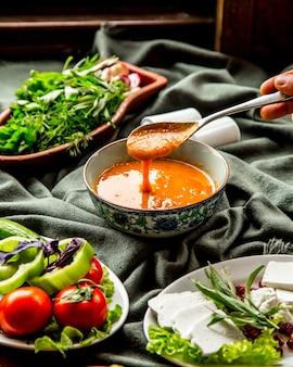 Вид спереди суп из чечевицы традиционный азербайджанский суп с ложкой над тарелкой в руке и с зеленью овощами и сыром на столе