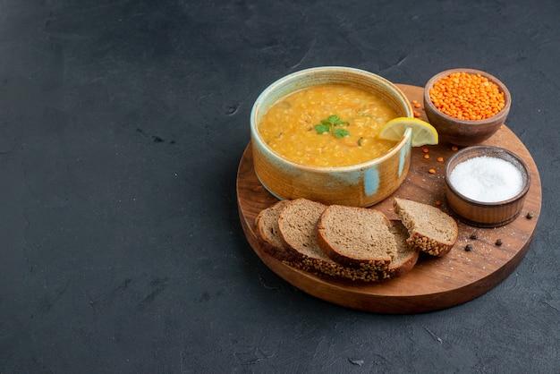 Суп из чечевицы, вид спереди с соленой сырой чечевицей и темными буханками хлеба на темной поверхности