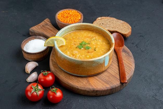 暗い表面に塩トマトと暗いパンのパンが入った正面図のレンズ豆のスープ