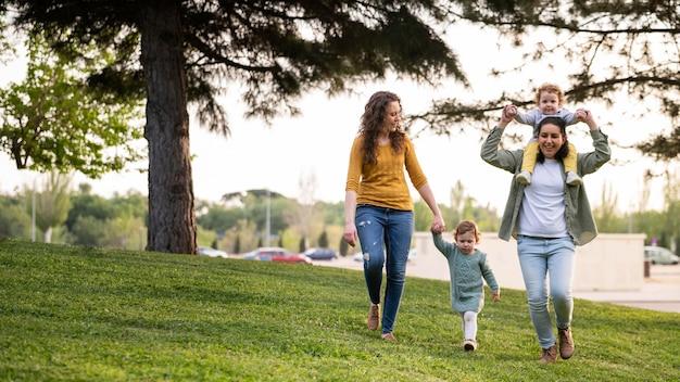 Vista frontale delle madri lgbt fuori nel parco con i loro figli