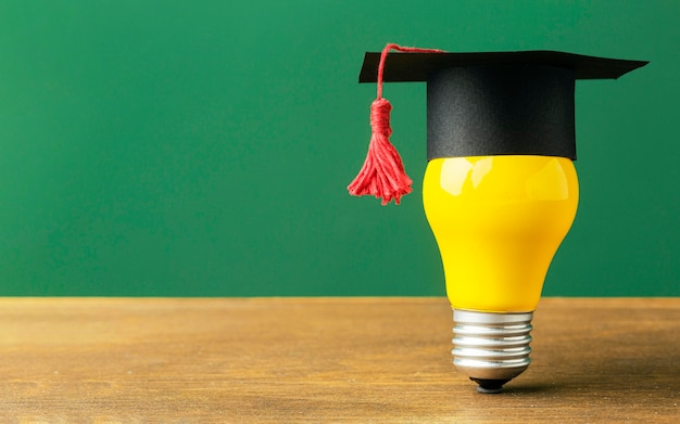 Front view of lightbulb with academic cap and copy space