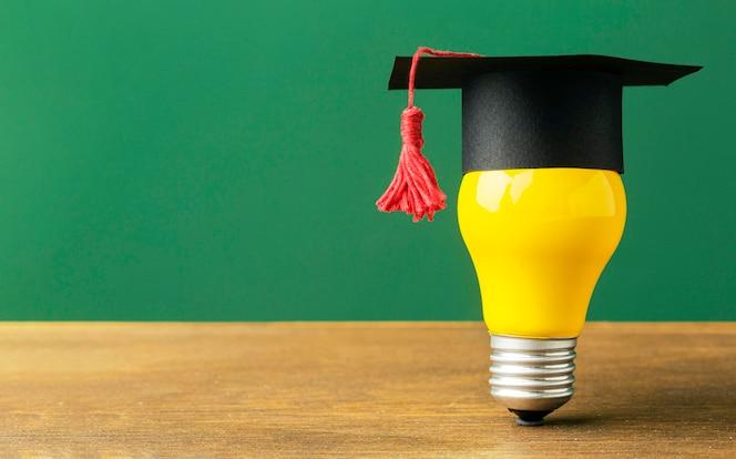 Vista frontale della lampadina con cappuccio accademico e copia spazio