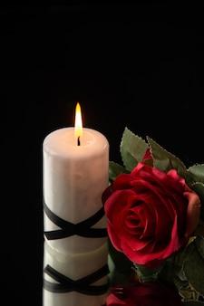 Vista frontale della candela accesa con fiore rosso su fondo nero