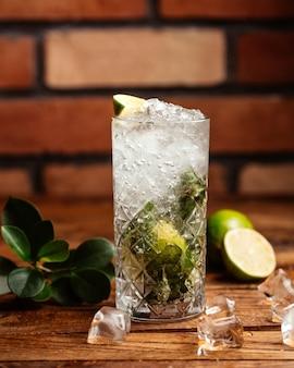 Un cocktail della calce di vista frontale con ghiaccio sulla frutta marrone della spremuta della bevanda della parete