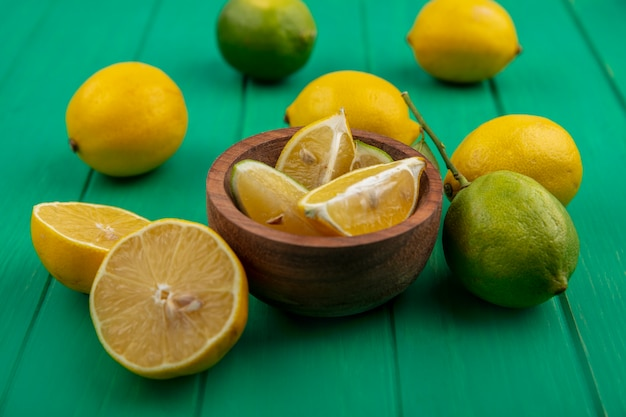 Дольки лайма с лимонами в деревянной миске на зеленом фоне, вид спереди
