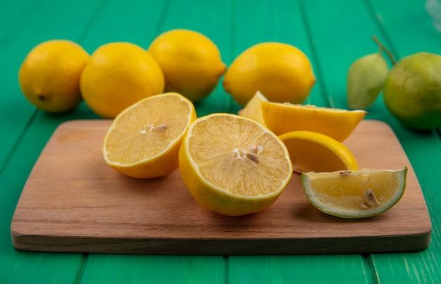 Дольки лайма с лимоном на разделочной доске на зеленом фоне, вид спереди