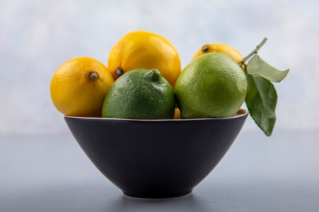 Front view limes and lemons in a black bowl on gray background