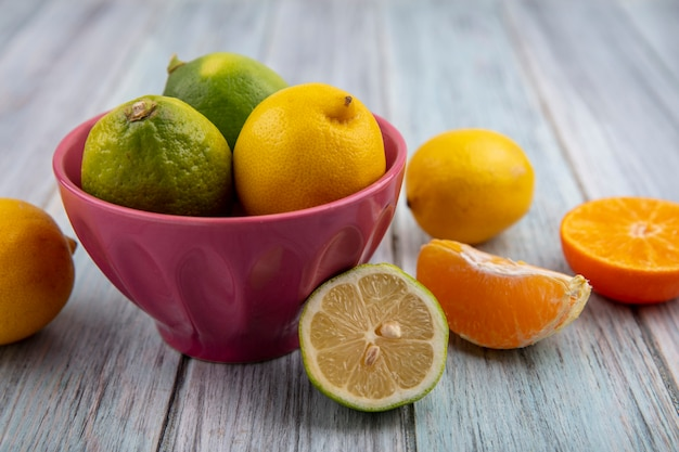 Front view limes with lemons in a bowl and orange slices on gray background