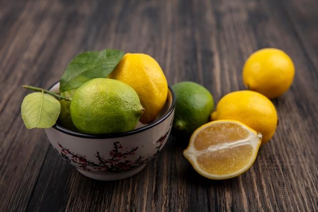 Vista frontale limette con limoni in una ciotola su sfondo di legno