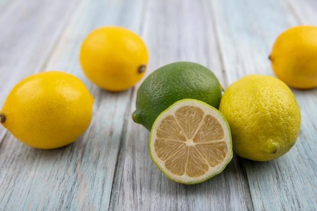 Лаймы с лимонами на сером фоне вид спереди