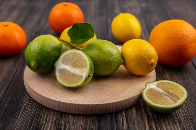 Vista frontale limette con limoni su un supporto con arance su uno sfondo di legno