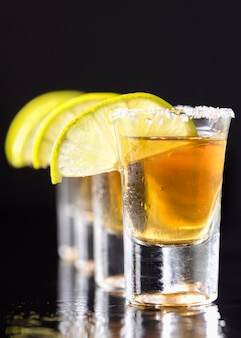 Front view line of gold tequila shots  with lime slices