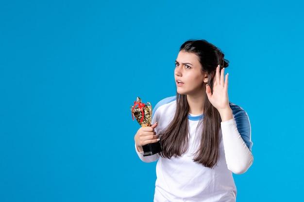 Вид спереди слушающего женского игрока с чашкой на синем