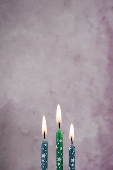 Front view of lit birthday candles with copy space