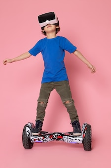 A front view little boy in blue t-shirt playing vr on segway on the pink space